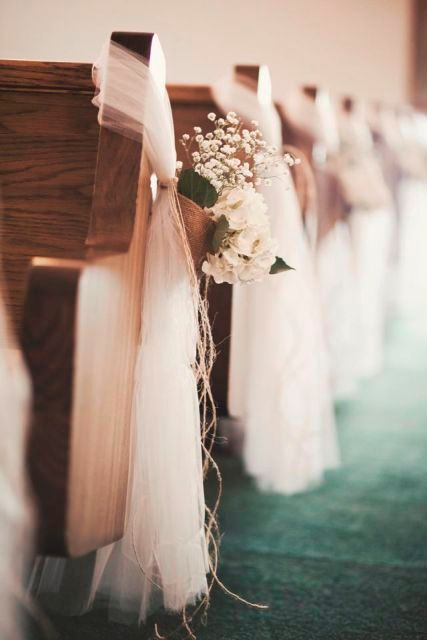 white tulle bench decor with baskets filled with baby's breath, white blooms and greenery