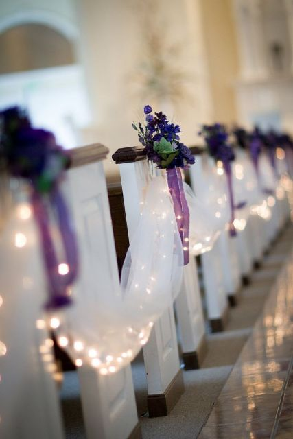 white tulle garlands with LEDs, purple blooms with greenery and purple bows