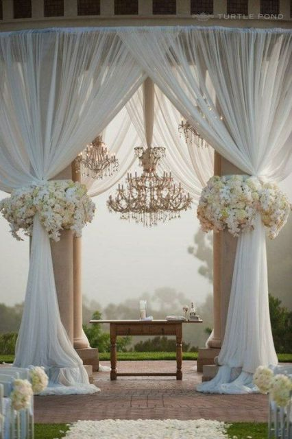a refined ceremony space with tulle curtains, a large chandelier and lush neutral florals