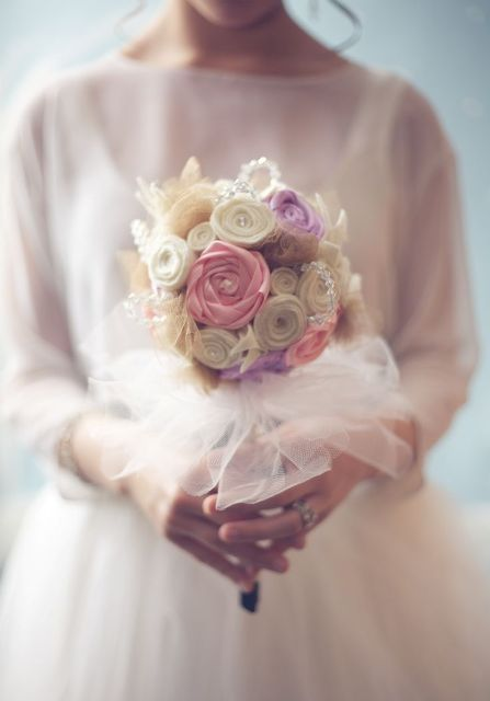 a fake bloom wedding bouquet with a white tulle wrap is eco-friendly and cool