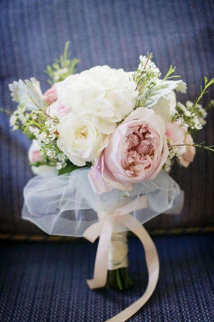 a lush pastel and neutral wedding bouquet with a tulel wrap and a bow