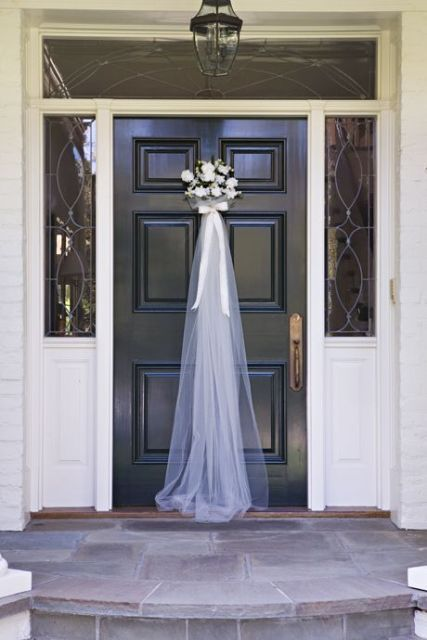 a floral arrangement with a bow and tulle on the door of your home on the day of your wedding