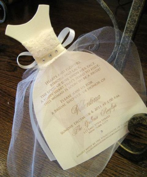 an invitation to a bridal shower shaped as a wedding dress with tulle covering it