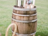 a barrel with calligraphy, photos and a candle lantern is a lovely rustic wedding decoration