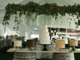 a wedding dessert station of wine barrels and a countertop plus several wedding cakes is a pretty and very easy idea