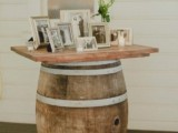 a lovely wedding decoration of a wine barrel and a countertop and lots of family pics and greenery is amazing for a rustic wedding
