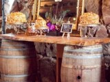 a wedding dessert bar with wine barrels and a countertop, a mirror in a refined frame and lots of various desserts