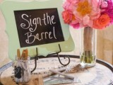 a wine barrel instead of a usual wedding guest book with bright blooms, a chalkboard sign, pens