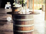 a wine barrel turned into a cocktail table with a tabletop, white blooms and greenery in bottles is amazing