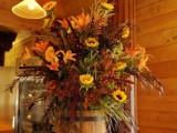 a small barrel used as a vase for a super bright rustic wedding floral arrangement