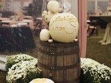 a barrel with white pumpkins, candles and blooms around is a lovely rustic or farmhouse wedding decoration