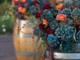 wine barrels used as stands for lush floral arrangements are a great idea for a vineyard wedding