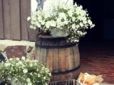 lovely rustic wedding decor with a barrel and a metal piece, floral arrangements, a wire basket and some bread is cool