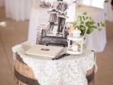 a pretty rustic vintage wedding decoration of a wine barrel with a doily, some photos, a candle lantern and greenery can be DIYed
