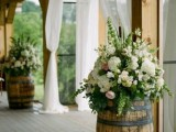 wine barrels as stands for floral arrangements can be used for vineyard, rustic weddings