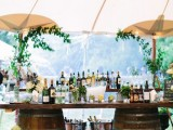 a wedding drink bar with wine barrels and a countertop, greenery, white hydrangeas and umbrellas over it is a lovely idea