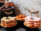 gilded trays with lots of glazed donuts and cute toppers are a nice idea for a wedding dessert table