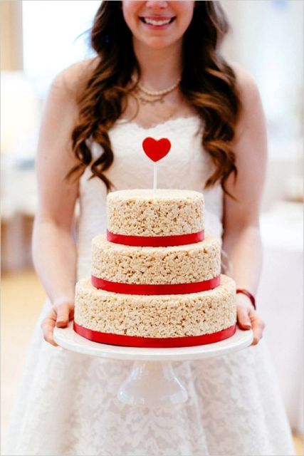 a krispie rice wedding designed as a usual one, decorated with red ribbons and a red heart topper