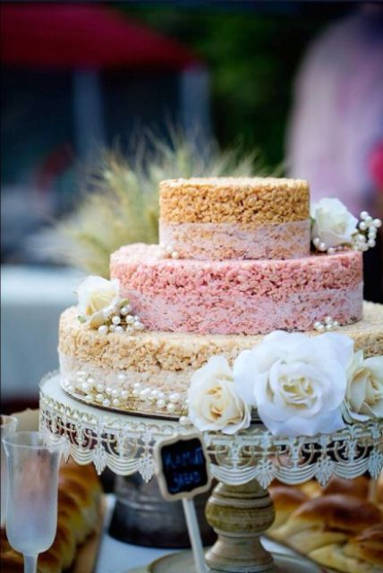 a round krispie rice wedding cake with a pink tier, lace ribbon and white blooms