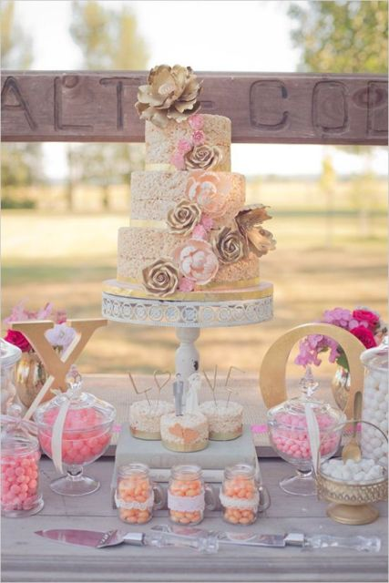a krispie rice wedding cake with gold ribbons and gold and pink sugar flowers