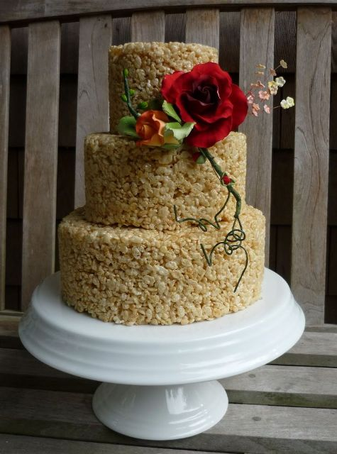 a krispie rice wedding cake decorated with sugar blooms and greenery is a sophisticated idea