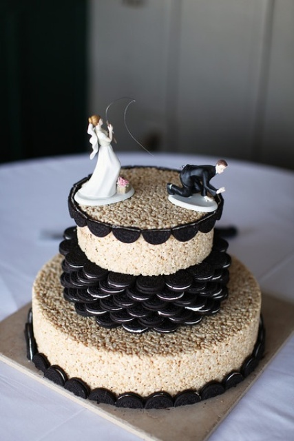 a krispie rice wedding cake with Oreos and funny sugar cake toppers is a creative modern idea