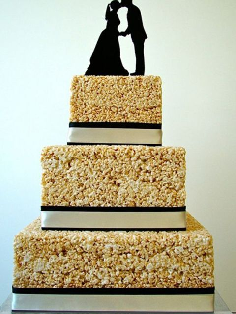 a square krispie rice wedding cake with ribbons and elegant silhouette cake toppers