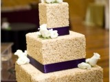 a square krispie rice wedding cake with purple ribbons, fresh white blooms is a refined and chic idea