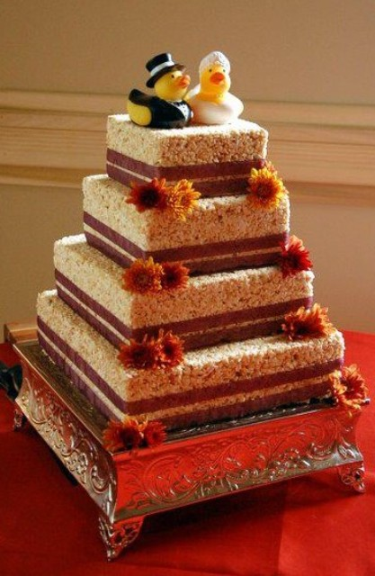 a large square krispie rice wedding cake with some blooms and with duck toppers for fun