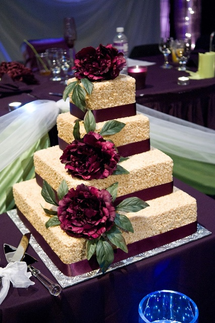 a square krispie rice wedding cake with purple ribbons and large purple blooms with greenery is a chic idea