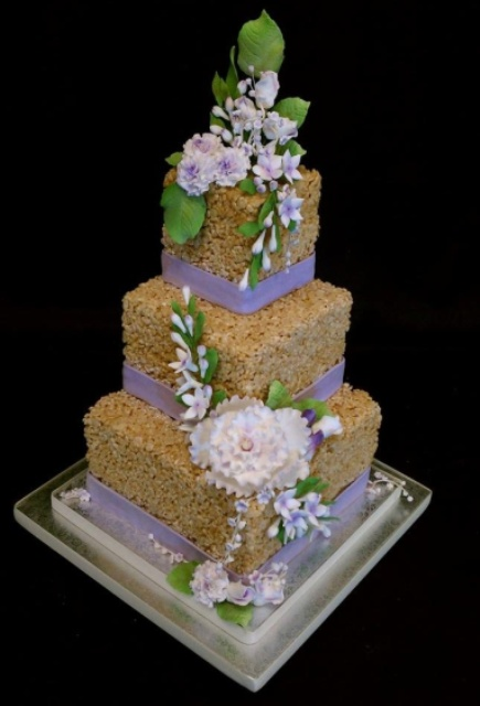 a square krispie wedding cake with lilac ribbons and lots of sugar blooms and greenery is a cool idea for spring