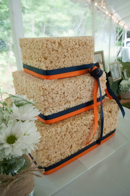 a square krispie rice wedding cake with navy and orange ribbons is a stylish and bold idea
