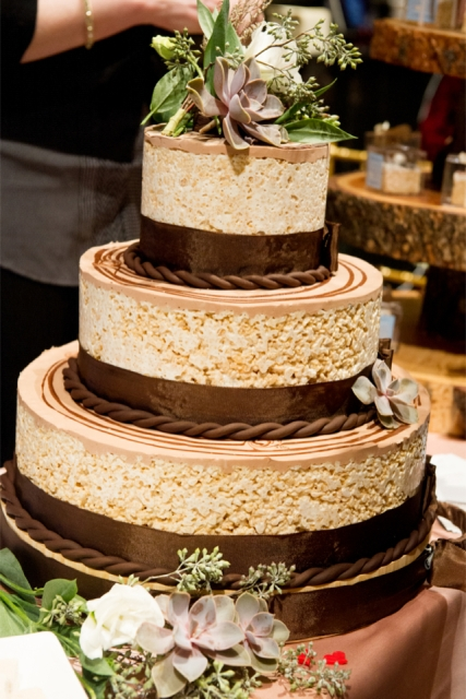 a round krispie rice wedding cake with ribbons, chocolate, fresh greenery, succulents and white blooms