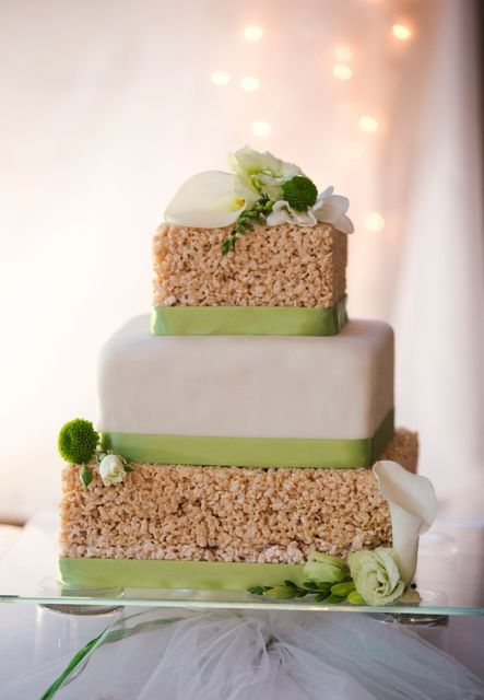 a krispie rice square wedding cake with a buttercream covered tier, green ribbons, white and green blooms