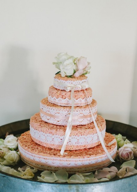 a krispie rice wedding cake with lace ribbons and white blooms on top looks very cute and rustic