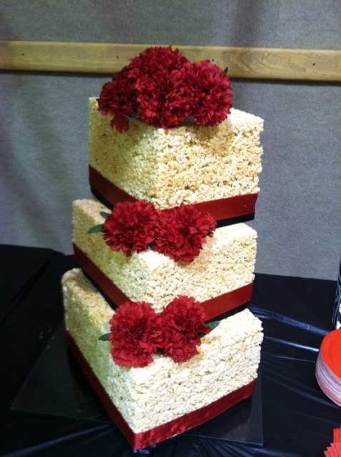 a square krispie rice wedding cake with red ribbons, red blooms looks refined