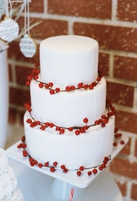 a white buttercream wedding cake decorated with berries is a simple and stylish idea for a winter wedding