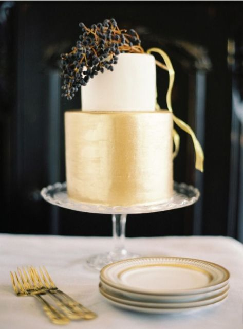 a refined modern winter wedding cake in gold and white topped with provet berries is a very chic option