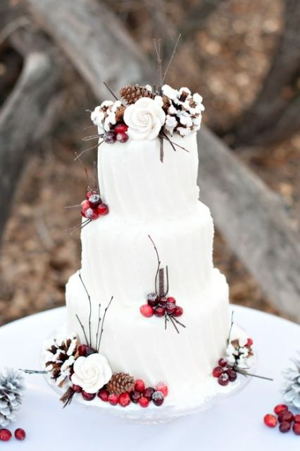 a white striped buttercream wedding cake decorated with twigs, cotton, berries and white flowers