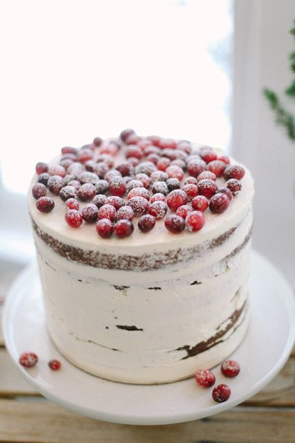 a naked wedding cake topped with sugared berries is a stylish and chic dessert for a winter wedding