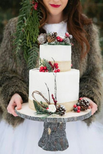 a winter wedding cake decorated with burlap ribbons, branches, berries, leaves and pinecones will fit a rustic celebration