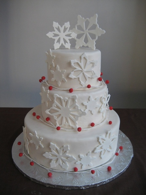 a white snowflake buttercream wedding cake with red berries is a stylish dessert for a winter celebration
