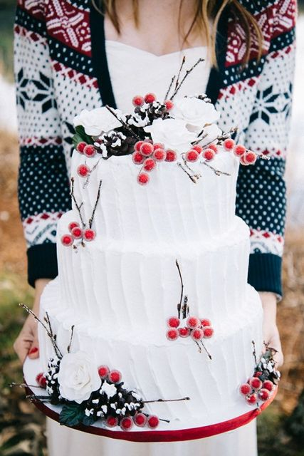 an oversized white striped wedding cake with white roses, twigs, berries and pinecones is a very chic and stylish idea