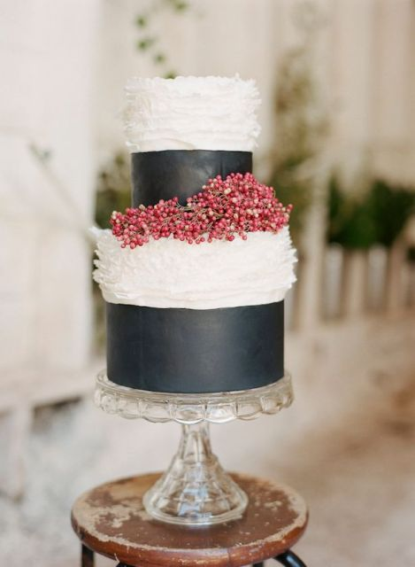a black and white wedding cake with mismatching dimensional tiers and red berries is a stylish idea for a winter wedding