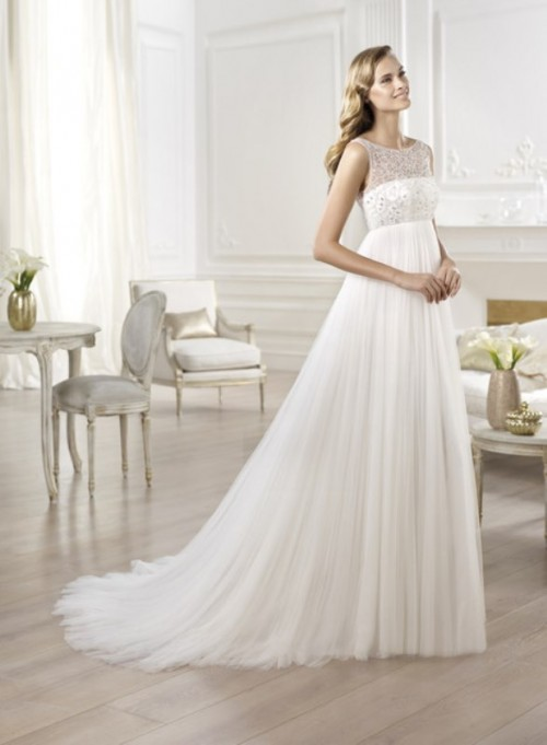 a romantic and elegant empire waist wedding dress with an embellished bodice, no sleeves and a train