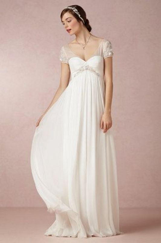 an elegant empire waist wedding dress with illusion sleeves, a draped bodice and pleated skirt