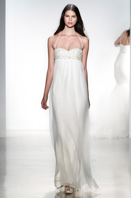 a fitting wedding dress with an embellished bodice, an empire waist, pleated skirt and spaghetti straps