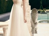 an empire waist wedding dress with an embroidered bodice, spaghetti straps and a pleated skirt with a train