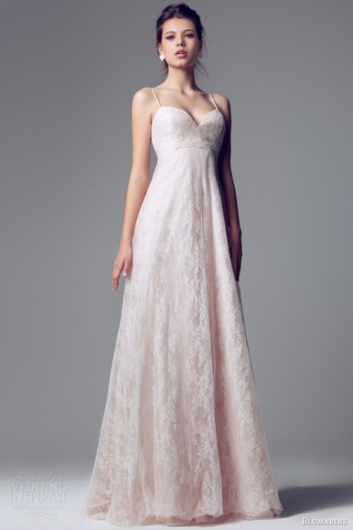 a classic blush lace A-line empire waist wedding dress with spaghetti straps and a pleated skirt plus statement earrings