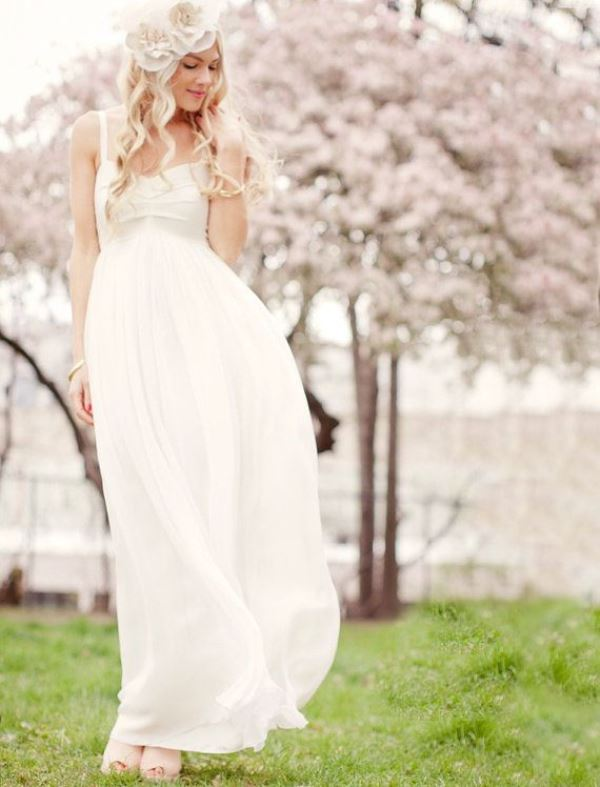 a casual white wedding dress with a draped bodice, an empire waist, a pleated skirt plus fabric blooms on the head